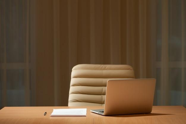 Mesa de escritório na sala vazia, computador portátil na mesa