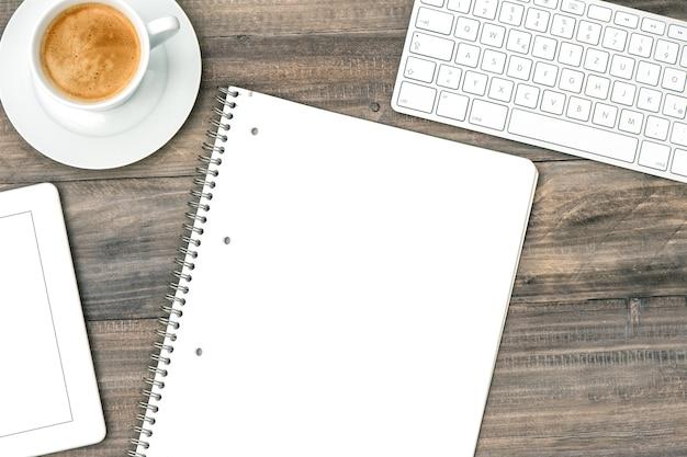 Mesa de escritório plana lay. tablet pc digital, teclado e café em fundo de madeira