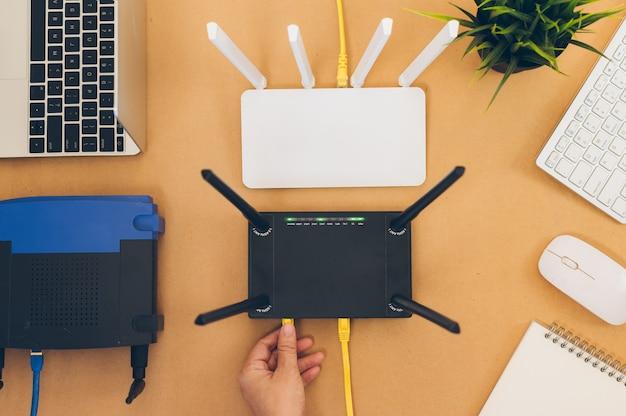 Mesa de escritório plana leigos com roteador wifi, computador e suprimentos vista superior