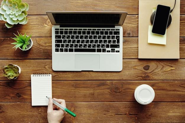 Mesa de escritório plana leigos espaço de trabalho com a mão feminina, vista superior do laptop