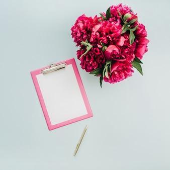 Mesa de escritório plana minimalista com prancheta, buquê de flores de peônia rosa na superfície azul