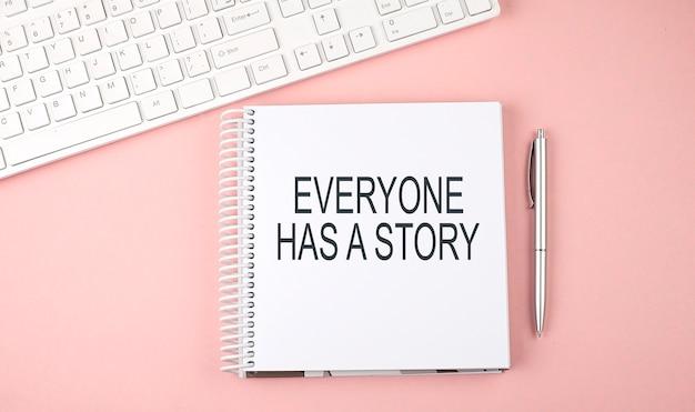 Mesa de escritório rosa com teclado e caderno com texto todos tem uma história