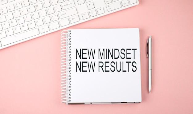 Mesa de escritório rosa com teclado e notebook com texto nova mente, novos resultados
