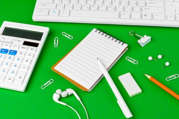 Mesa de escritório verde com artigos de papelaria branco, copie o espaço
