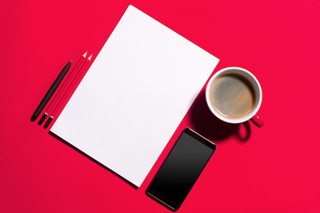 Mesa de escritório vermelha moderna com smartphone e xícara de café.