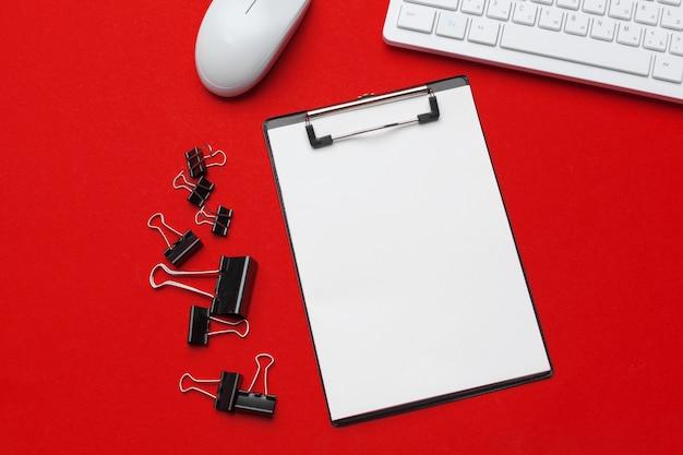 Mesa de escritório vermelho com artigos de papelaria e material de escritório