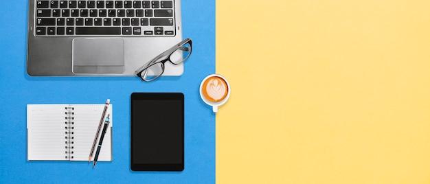 Mesa de escritório vista superior com laptop, tablet, caderno em branco e café em fundo colorido