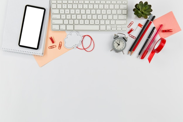 Mesa de escritório vista superior com telefone e teclado Foto gratuita
