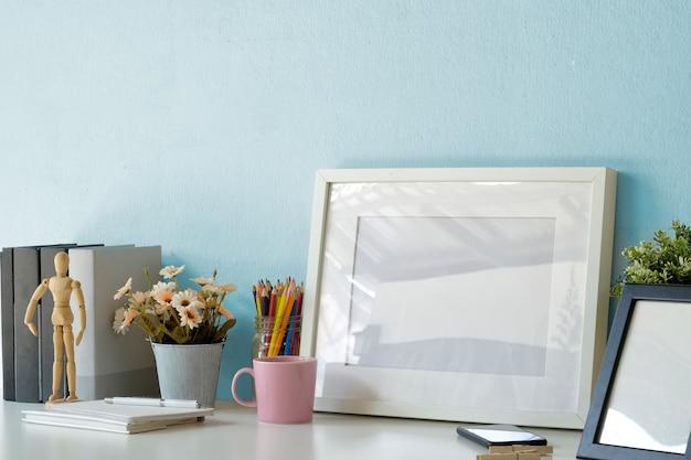 Mesa de espaço de trabalho de maquete com quadro de cartaz branco, caneca de café, caderno e suprimentos.