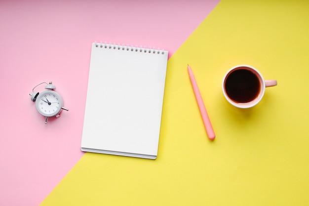 Mesa de estudante com suprimentos, notebook, xícara de café, caneta, mini despertador.