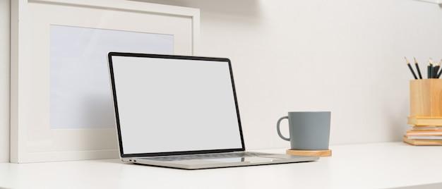 Mesa de estudo moderno com mock-se laptop, xícara de café, mock-se quadro e artigos de papelaria na mesa branca