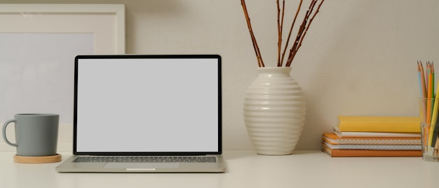 Mesa de estudo moderno com mock up laptop, artigos de papelaria, livros e decorações na mesa branca