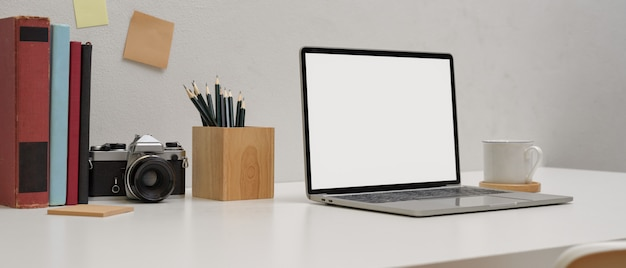 Mesa de estudo simples com mock up laptop, lápis, bloco de notas, câmera, livros, copo