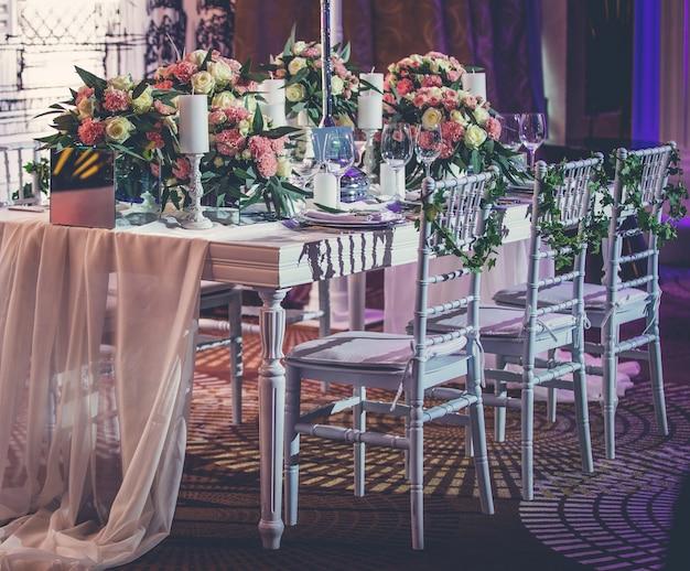 Mesa de evento de noivado com toalha de mesa de tule e flores