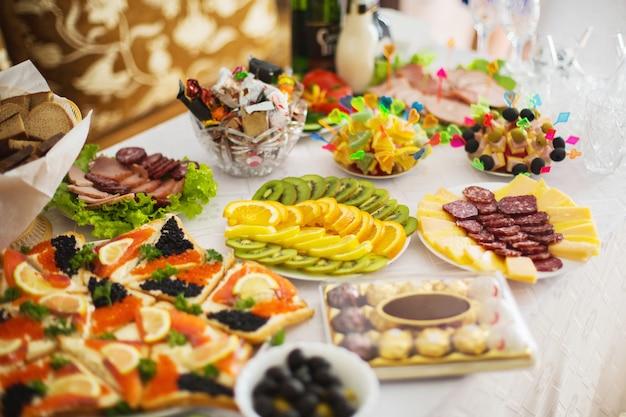 Mesa de férias com sanduíches com caviar, frutas e legumes, com carne picada