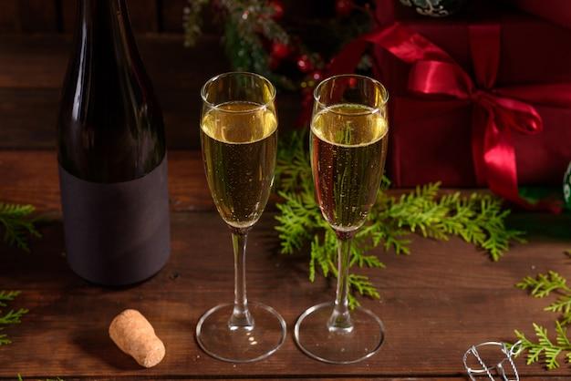 Mesa de férias de natal com copos e uma garrafa de vinho de champanhe