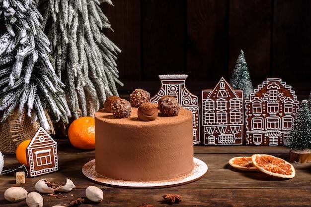 Mesa de férias de natal com delicioso bolo de trufas e lindos biscoitos de gengibre. clima festivo na véspera de natal