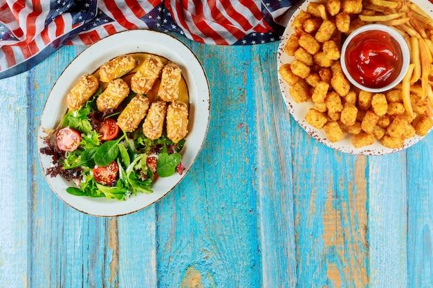 Mesa de festa americana com batata frita, ketchup e vegetais.
