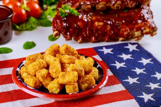 Mesa de festa com batata frita e costeletas de vaca para o dia dos veteranos.