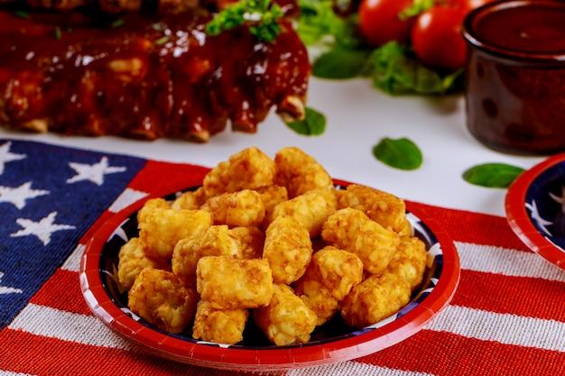 Mesa de festa com batatas tater e costelas de churrasco para o dia da independência.
