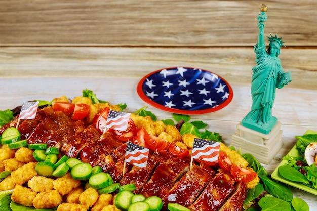 Mesa de festa com comida e estátua da liberdade. conceito de feriado americano.