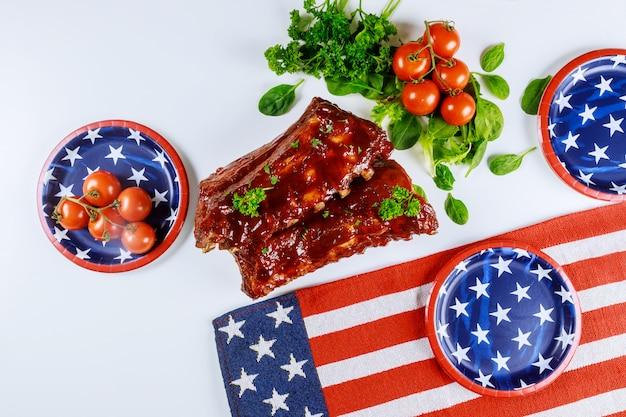 Mesa de festa com costelas de churrasco e bandeira americana.