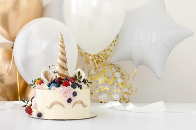 Mesa de festa de aniversário com bolo de unicórnio