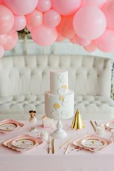 Mesa de festa de aniversário de menina com lindo bolo. cenário de mesa decorado guirlanda rosa ballond