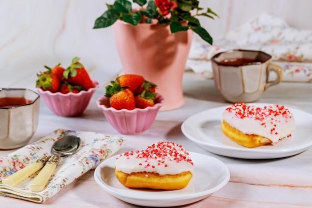 Mesa de festa de chá com rosquinhas em forma de coração, morango e rosa.