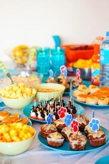 Mesa de festa decorada com diversas sobremesas e petiscos