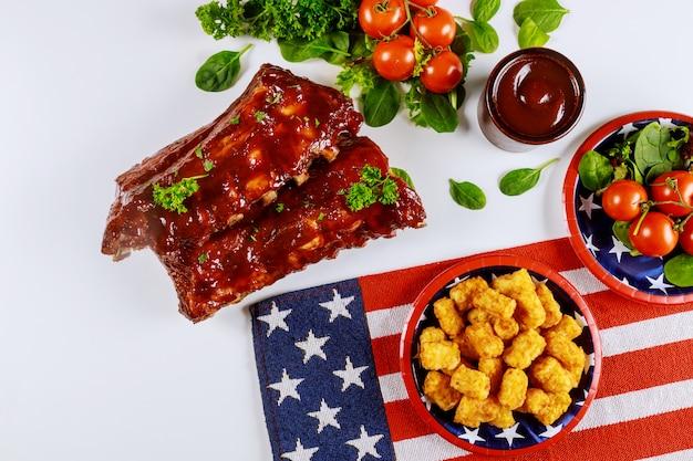 Mesa de festa festiva com batata, costelas e vegetais para o feriado americano.