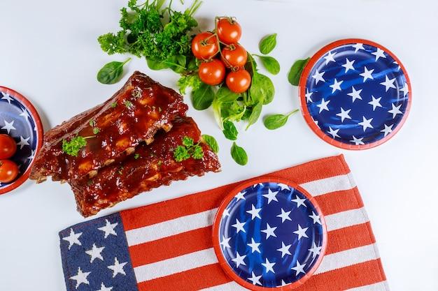 Mesa de festa festiva com costelas e vegetais para o feriado americano.