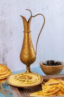Mesa de festa turca com hummus, pão e jarro de cobre.