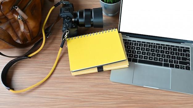 Mesa de fotógrafo com câmera e lente, bolsa para câmera, computador portátil, papel de caderno.