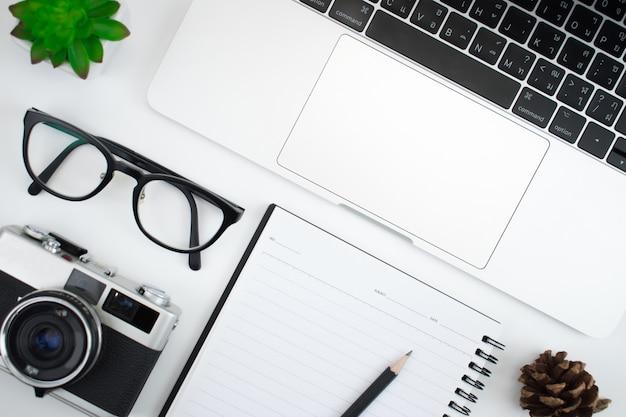 Mesa de fotógrafo com câmera, laptop e óculos prontos para trabalhar em uma mesa branca, vista superior