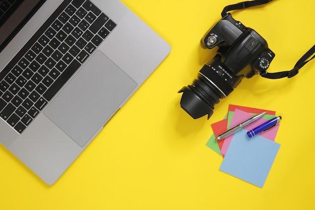 Mesa de fotógrafos com adesivos de papel, câmera de computador e adesivos de papel em fundo amarelo
