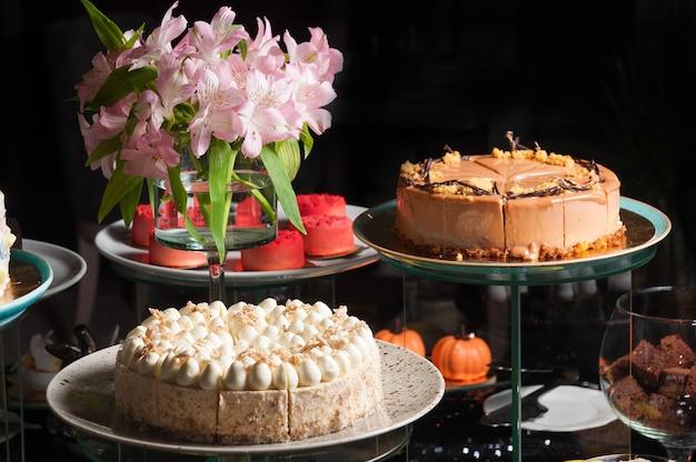 Mesa de fundo escuro com bolos e doces artesanais
