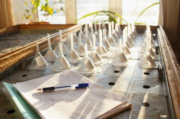 Mesa de germinação com sementes em funis de filtro e diário de bordo com caneta