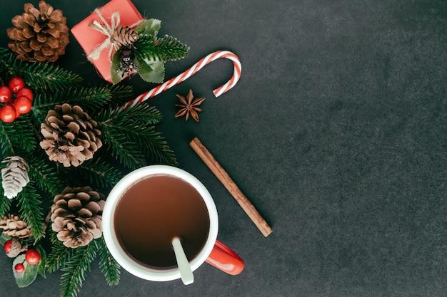 Mesa de granito preto com caixa de presente, folha de pinheiro e cones, bolas de azevinho e xícara de chocolate
