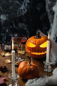 Mesa de halloween com jack o lanterna, teia de aranha, velas e fumaça