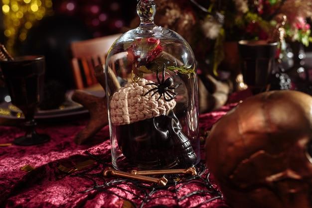Mesa de halloween decorada com alguns enfeites assustadores, como uma caveira, um morcego preto ou uma abóbora esculpida
