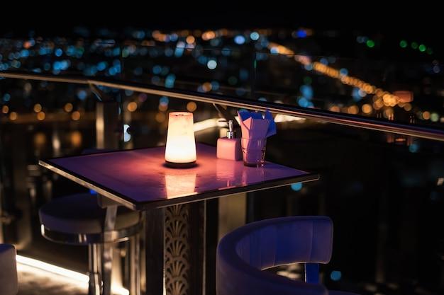 Mesa de jantar ao ar livre no telhado com borrão bokeh cidade luz. pub e restaurante de luxo