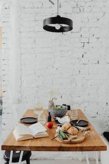 Mesa de jantar bagunçada com um livro