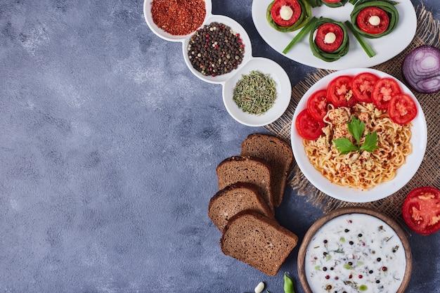 Mesa de jantar com comida mista em pratos brancos em um pedaço de serapilheira.