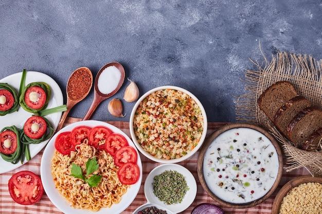 Mesa de jantar com comida mista em pratos brancos.