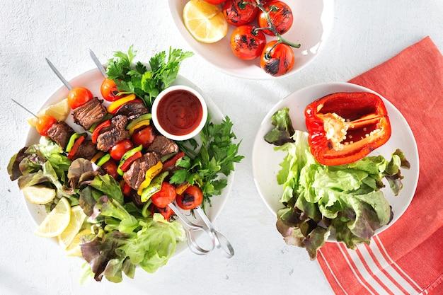 Mesa de jantar com kebab de carne grelhada com legumes e molho vista superior
