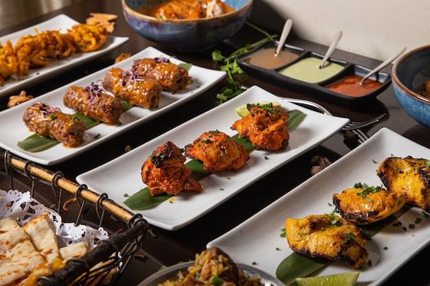 Mesa de jantar com pratos de carnes fritas e molhos