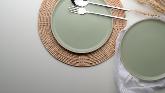 Mesa de jantar com pratos de cerâmica turquesa e talheres no tapete e guardanapo na mesa branca