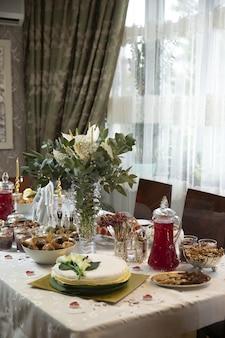 Mesa de jantar com refeições e flores decorativas, vista de alto ângulo em uma sala