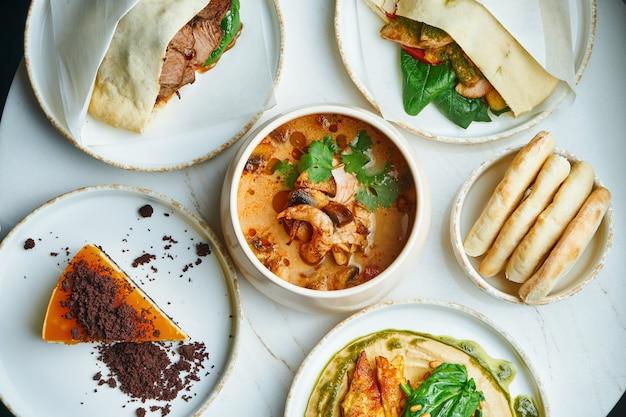 Mesa de jantar com uma grande variedade de pratos - pita com carne, homus, sopa de frutos do mar e bolo de queijo em uma superfície de mármore. vista superior, comida plana leigos